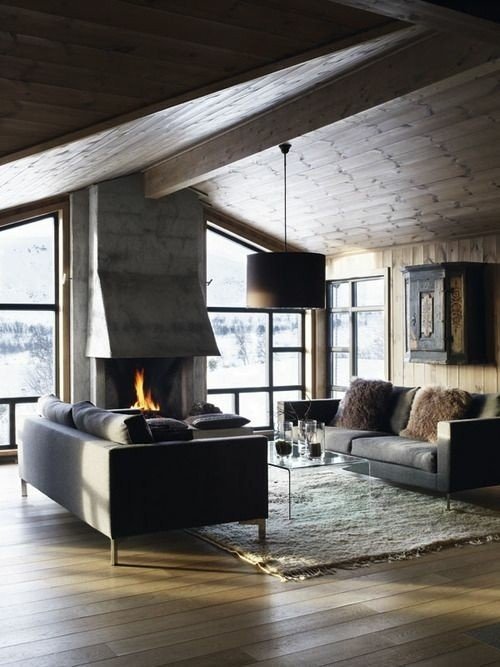 chalet bois beton cheminee feu foyer coussins planche