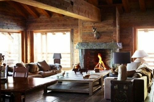 sejour chalet fenetre table basse divan cheminee feu