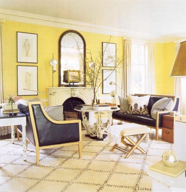salon murs jaunes déco miroir fauteuil noir en cuir table basse salon canapé en cuir miroir tableaux déco