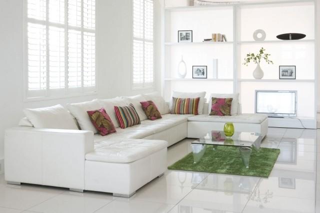 petite-table-salon-transparente-verre-canapé-angle-blanc-moderne-coussins table de salon