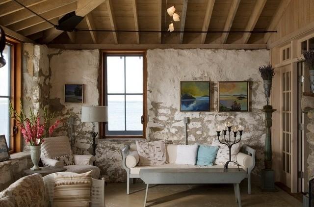 déco-salon-rustique-murs-pierre-exposés-bois-mobilier-blanc-élégant-bougeoir-fer-forgé-noir déco salon rustique