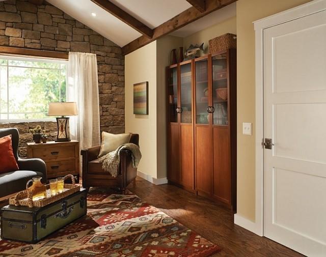 déco-salon-rustique-pierre-paremenr-murs-commode-bois-tapis-motifs-fauteuil-cuir-marron déco salon rustique