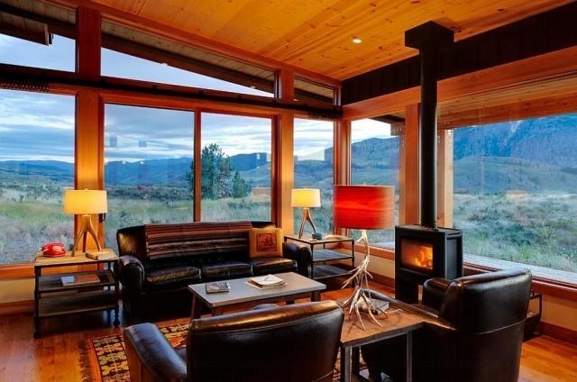 déco-salon-rustique-plafond-bois-canapé-fauteuils-cuir-noir-poêle-bois-lampes-poser-élégantes déco salon rustique