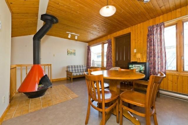 séjour en style rustique canapé deux place table en bois chaise en bois rideaux