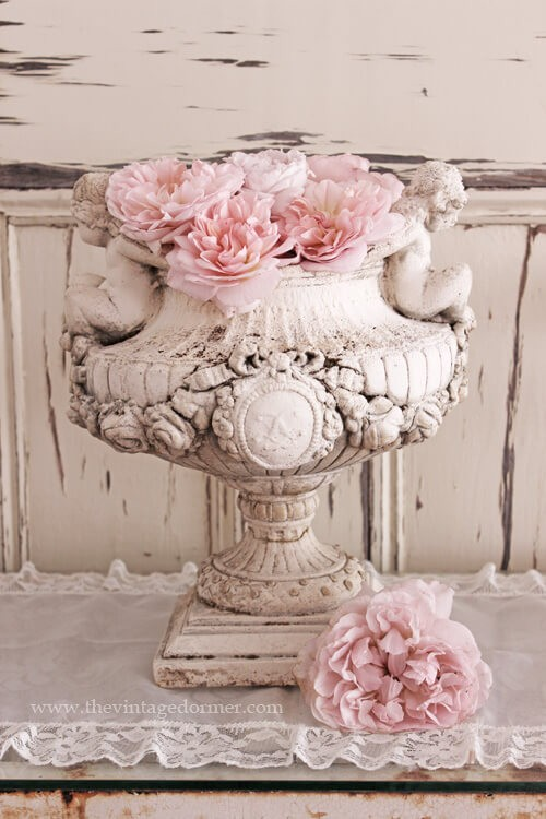 Ancienne jardinière sur piédestal avec des fleurs roses