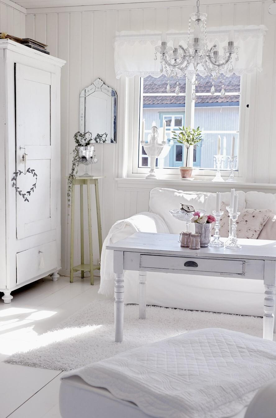Chambre toute blanche avec des touches de rose