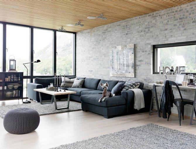 Salon industriel avec grand canapé, chaises et au mur de briques