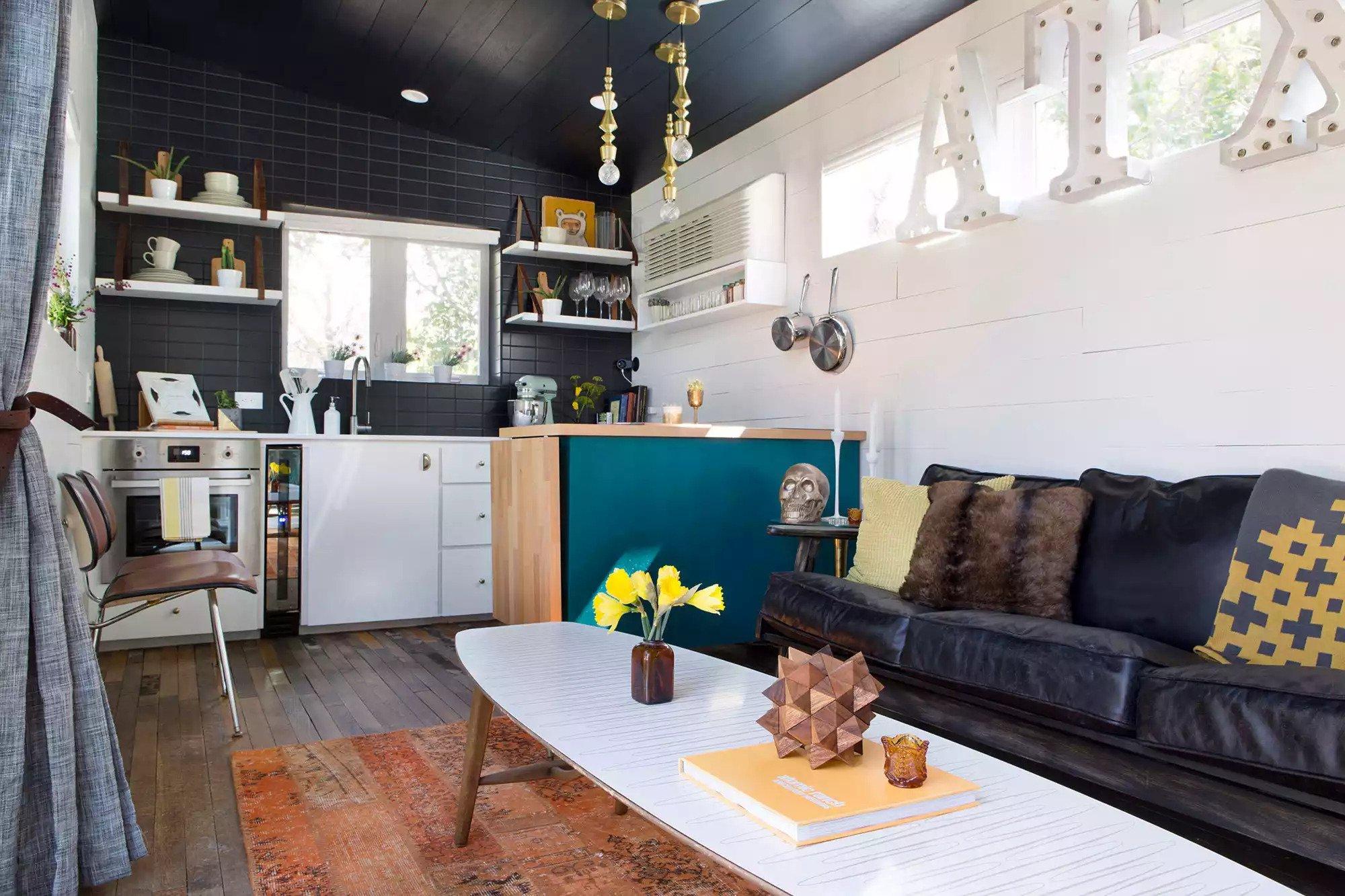 Petite maison avec un canapé en cuir noir