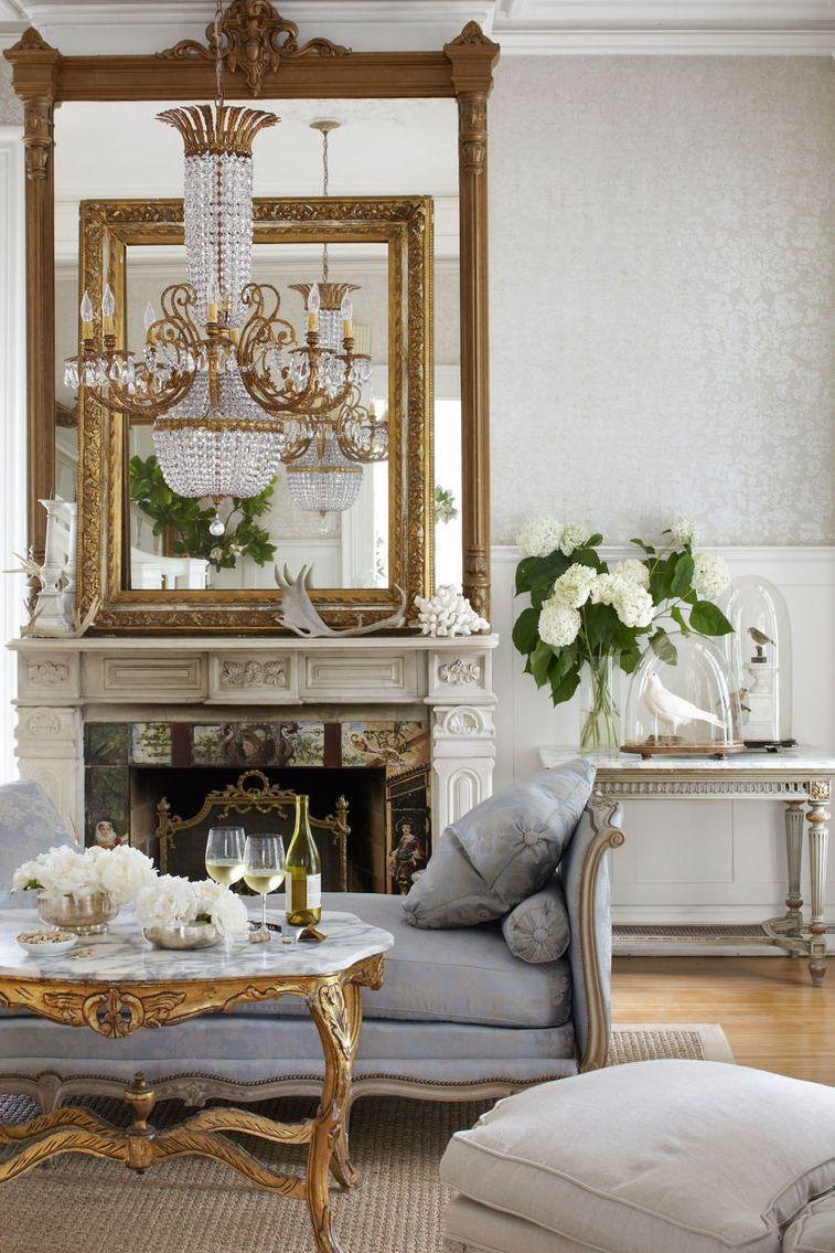 Salon avec des miroirs dorés sur la cheminée et un chandelier devant celle-ci