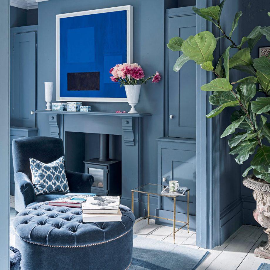 Un salon bleu foncé avec un poêle à bois gris ton sur ton dans une cheminée à foyer victorien
