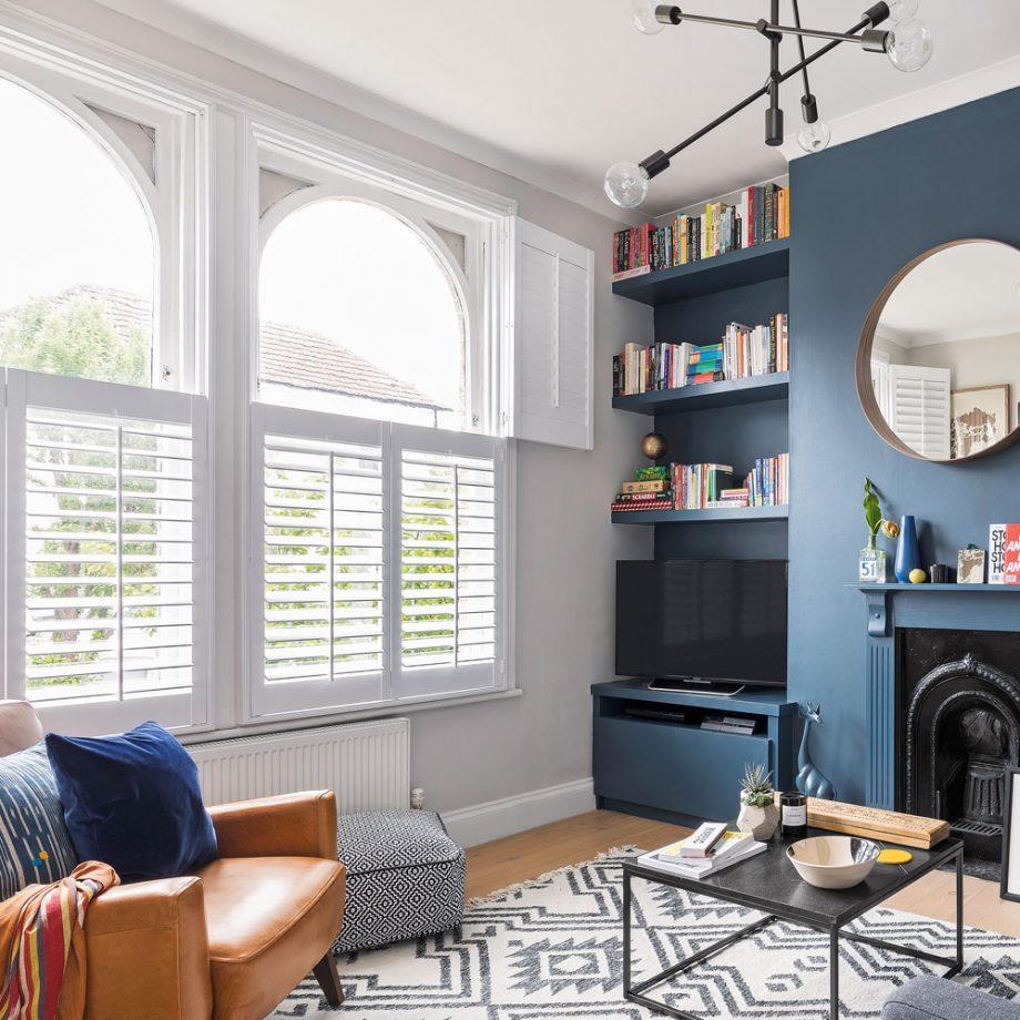 salon bleu avec volets de style café aux fenêtres cheminée victorienne noire et étagères encastrées dans des renfoncements