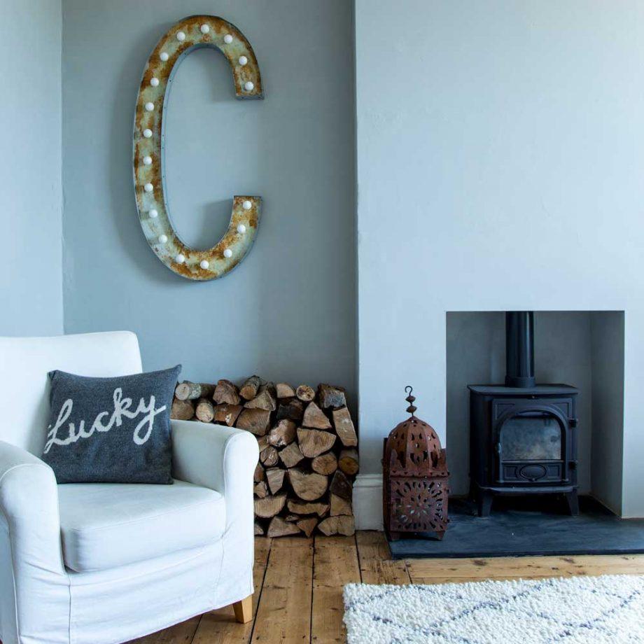 un salon bleu clair dans une propriété victorienne avec un plancher d'origine et un poêle à bois